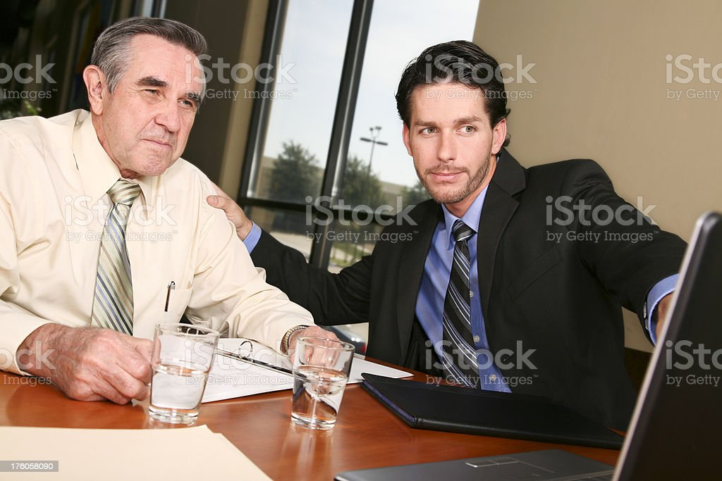 Business colleagues discussing something on a laptop royalty-free stock photo
