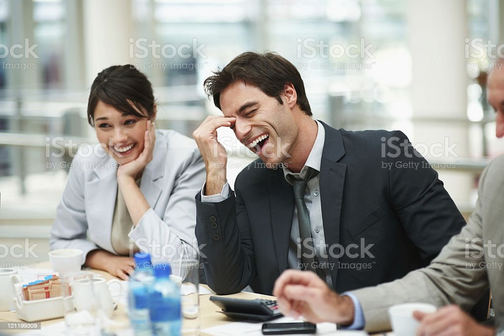 Business colleagues enjoying a laugh at meeting royalty-free stock photo