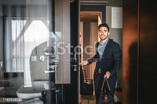 Reflective view of male and female Caucasian executives entering naturally lit modern hotel room with luggage.