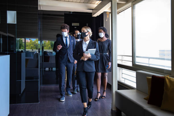 Business colleagues entering the office wearing protective face masks stock photo