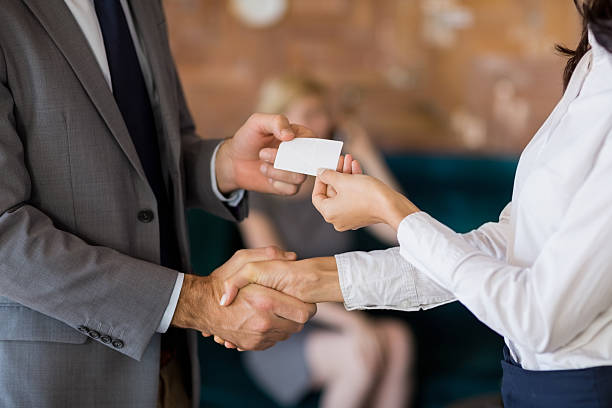 business colleagues exchanging business card - business card stock photos and pictures