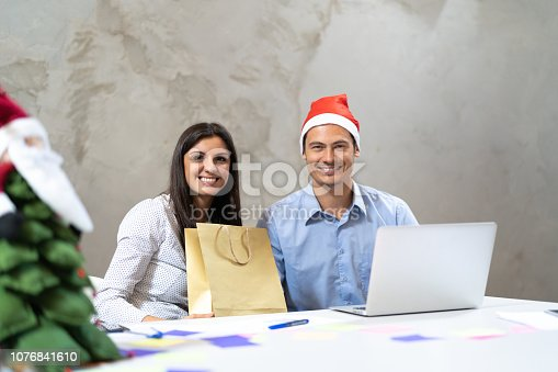 istock Business colleagues Exchanging Christmas presents at work / Amigo Secreto 1076841610