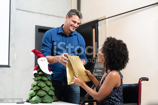 istock Business colleagues giving christmas presents at work / Amigo Secreto 1076679652