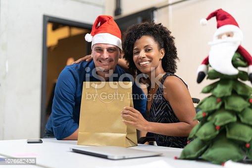 istock Business colleagues giving christmas presents at work / Amigo Secreto 1076682438