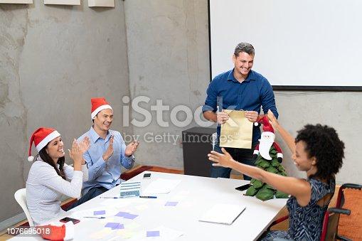 istock Business colleagues giving christmas presents at work / Amigo Secreto 1076695018