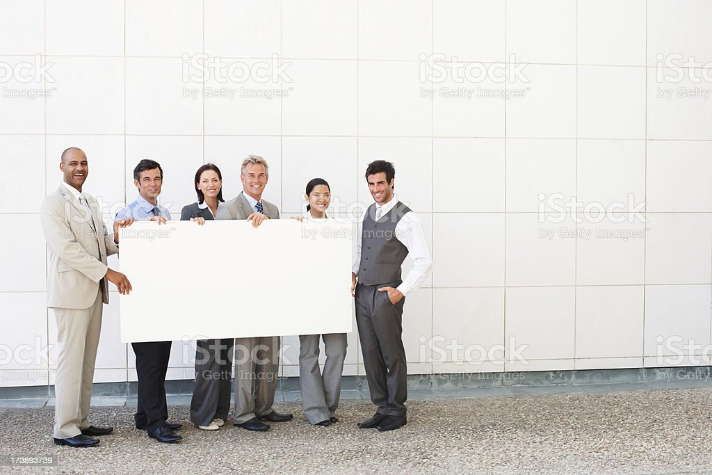 Business colleagues holding billboard royalty-free stock photo