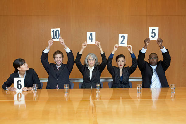 business colleagues holding up cards with numbers - judgement stock pictures, royalty-free photos & images