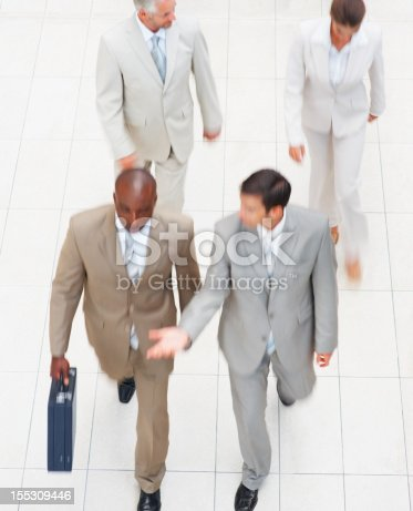 905689676 istock photo Business colleagues in a discussion while walking 155309446