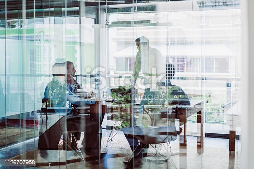 Business colleagues in meeting at office. Male and female professionals are planning strategy in brightly lit workplace. They are seen through glass wall with reflections.