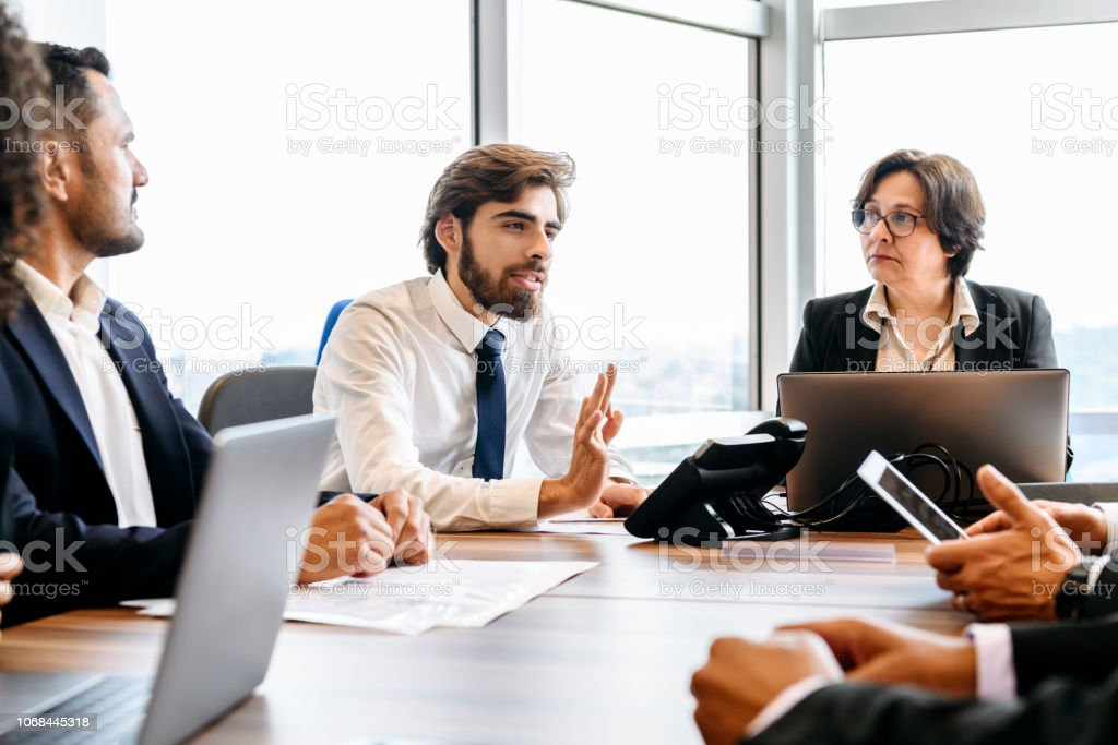 Business colleagues in meeting with laptops Young man explaining and gesturing with hand, mature woman listening, busy team having meeting at work, discussion, brainstorming 20-24 Years Stock Photo