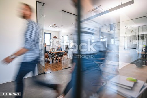 1163429625istockphoto Business Colleagues in Motion Past Office Conference Room 1163429480