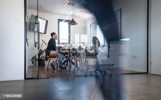 1163429625istockphoto Business Colleagues in Motion Past Office Conference Room 1163429483