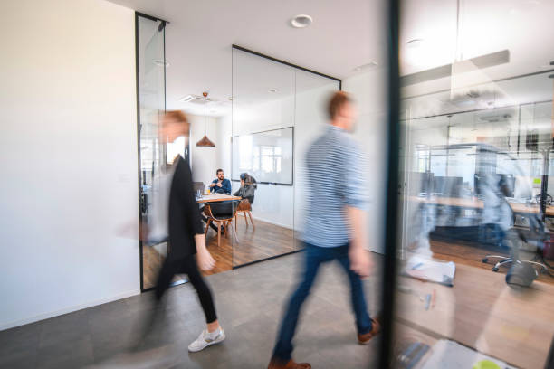 business colleagues in motion past office conference room - modern office foto e immagini stock