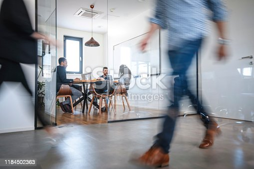Blurred motion of male and female businesspeople walking down hallway contrasted by still and careful debate of new ideas in the conference room.