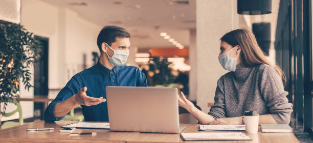 business colleagues in protective masks sitting at the office Desk close up. business colleagues in protective masks sitting at the office Desk. business stock pictures, royalty-free photos & images