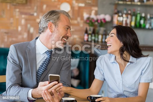 Business colleagues interacting with each other while having tea in restaurant