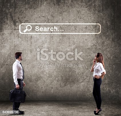 Businessman and businesswoman looking at website search engine icon