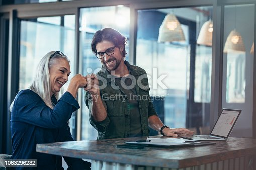 istock Business colleagues making a fist bump at office 1063296232