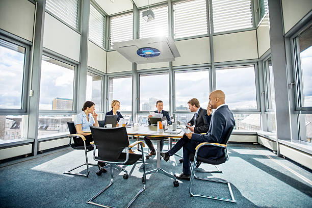 Business colleagues meeting in conference room Business colleagues having meeting in conference room in modern office governing board stock pictures, royalty-free photos & images