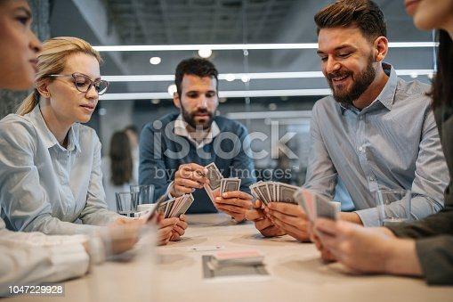 Group of business colleagues playing poker with cards on a break in the office.