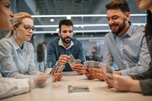 Business colleagues playing cards on a break in the office.
