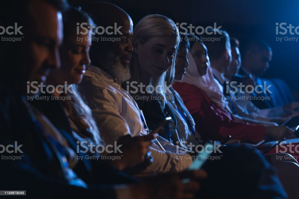 Side view of mixed race business colleagues sitting and holding...
