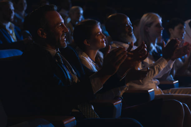 business colleagues sitting and watching presentation with audience and clapping hands - audience clapping stock photos and pictures
