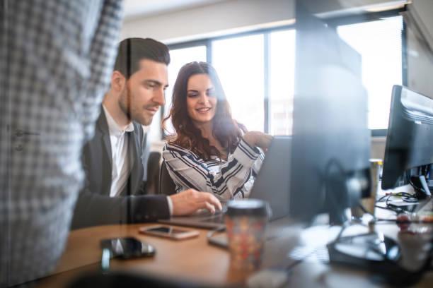 Geschäftskollegen, die am Arbeitsplatz sitzen und Ideen austauschen – Foto