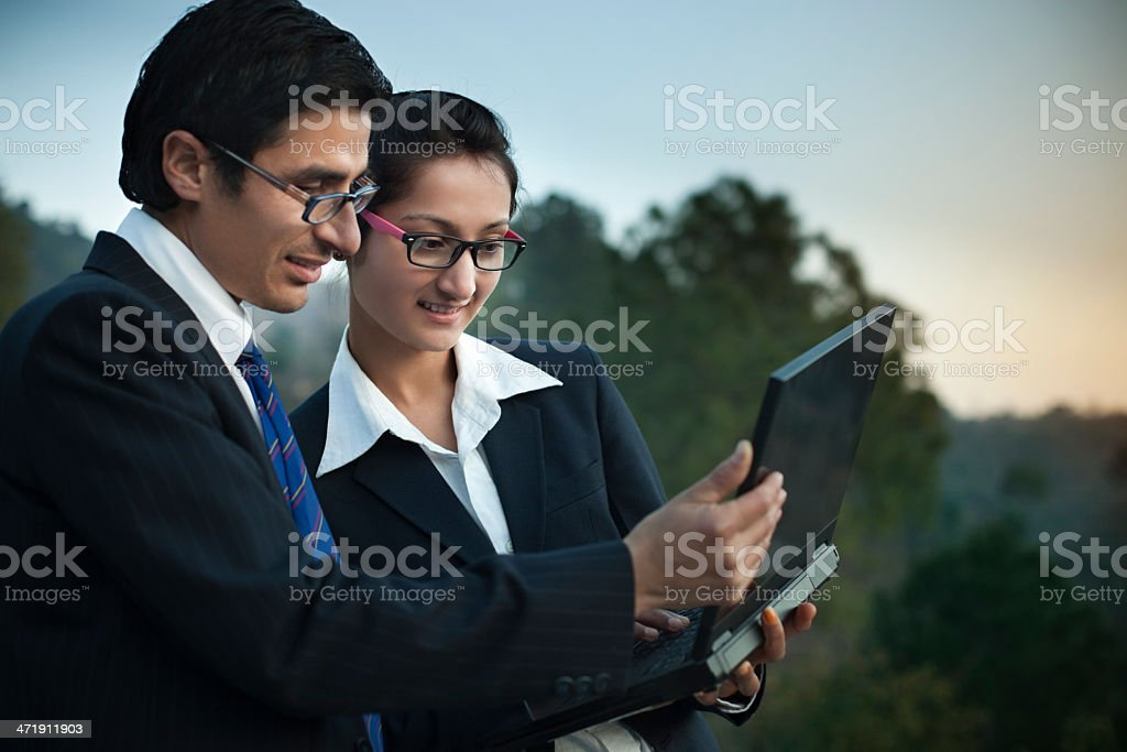 Business colleagues standing together, using laptop in outdoor. royalty-free stock photo