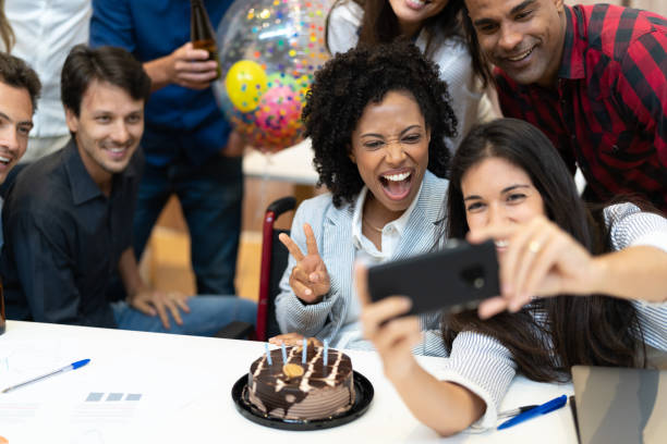 Business colleagues taking a selfie at birthday party at work Place of Work customs stock pictures, royalty-free photos & images