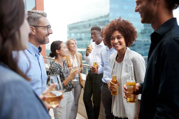 colegas do negócio que falam e que bebem junto em um balcão na cidade após o trabalho - happy hour - fotografias e filmes do acervo