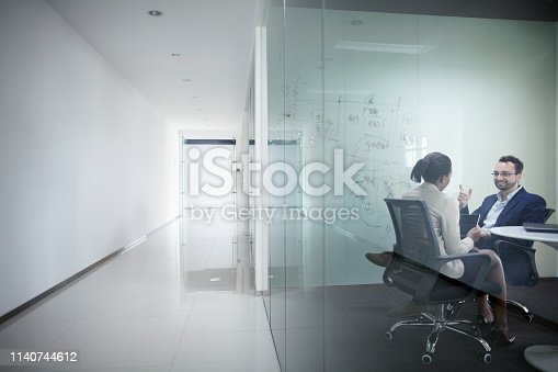 Pair of business colleagues co-workers staff members sitting in modern contemporary startup tech glass meeting room office with drawing board discussing and talking about new ideas and innovation creativity planning together for future success