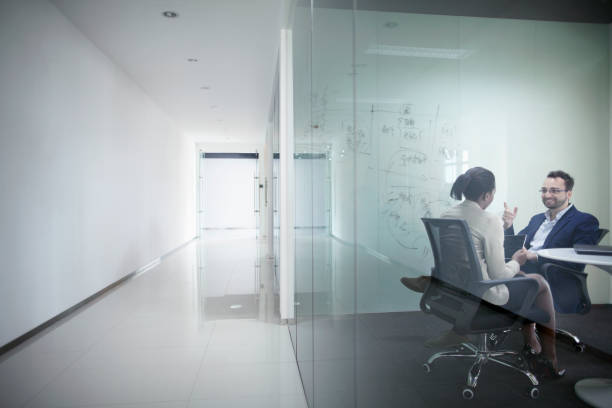 Business colleagues talking in glass meeting room stock photo