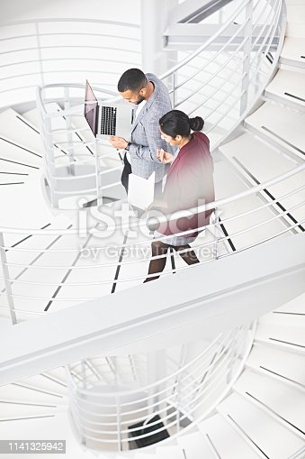 Business colleagues talking while walking down stairway