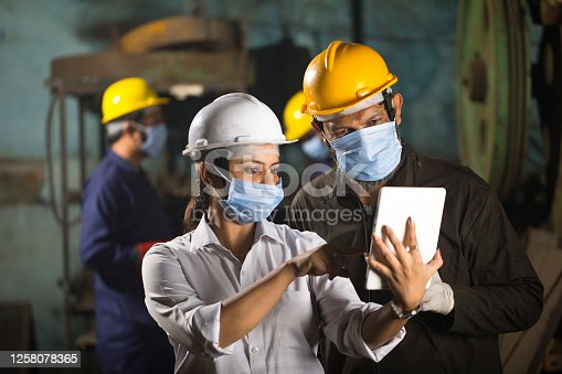 Business colleagues using digital tablet at factory