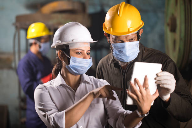 Business colleagues using digital tablet at factory stock photo