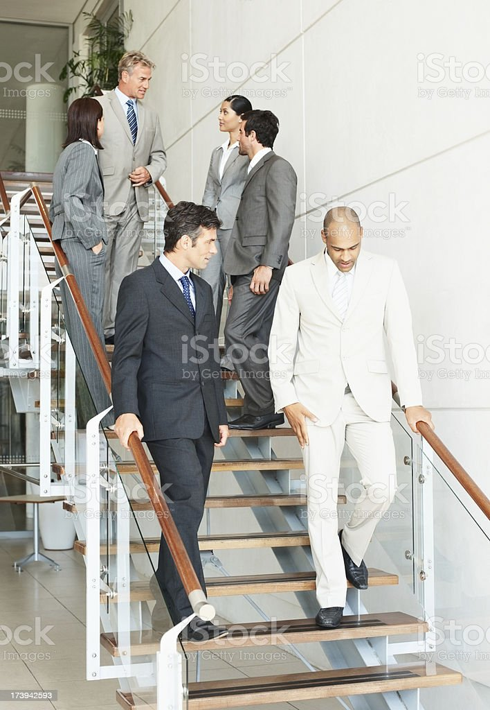 Business colleagues walking down stairs stock photo