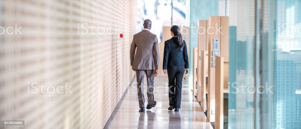 Business colleagues walking in office stock photo