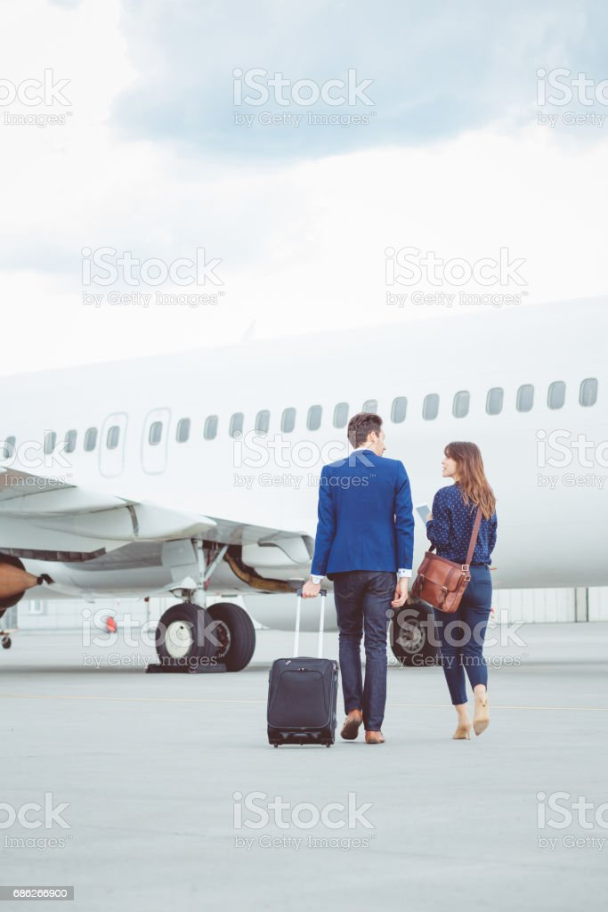 Business colleagues walking on tarmac at the airport stock photo