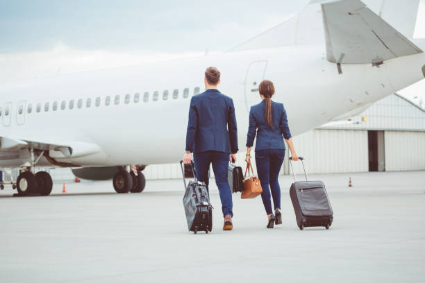 business colleagues walking on tarmac at the airport - getting on stock photos and pictures