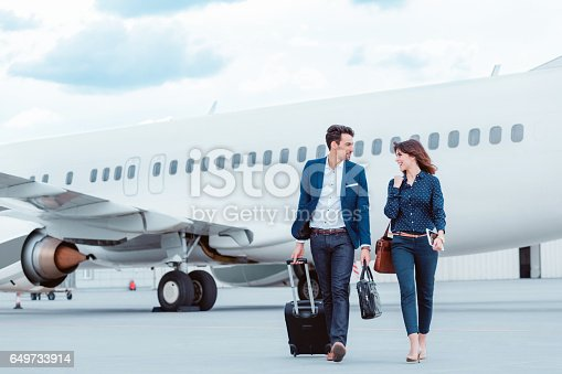 istock Business colleagues walking on tramac in front of airplane. 649733914
