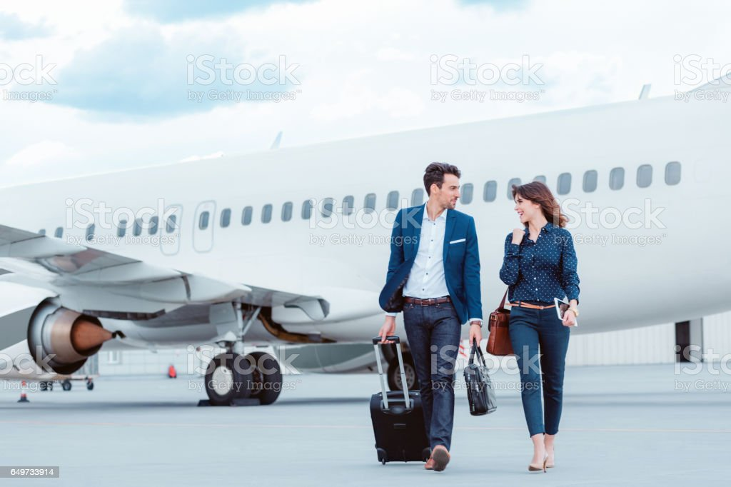Business colleagues walking on tramac in front of airplane. stock photo
