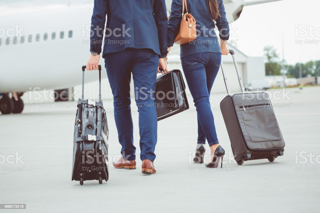 Business colleagues walking towards the airplane stock photo