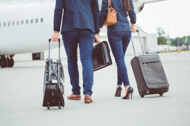 business colleagues walking towards the airplane - business travel stock photos and pictures