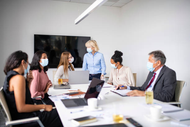 Business Colleagues Wearing Protective Masks During Meeting stock photo