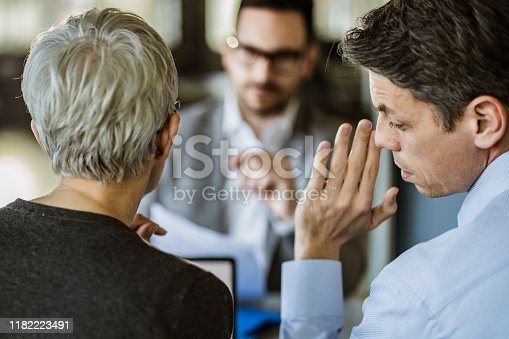 Members of human resource team whispering during a job interview in the office.