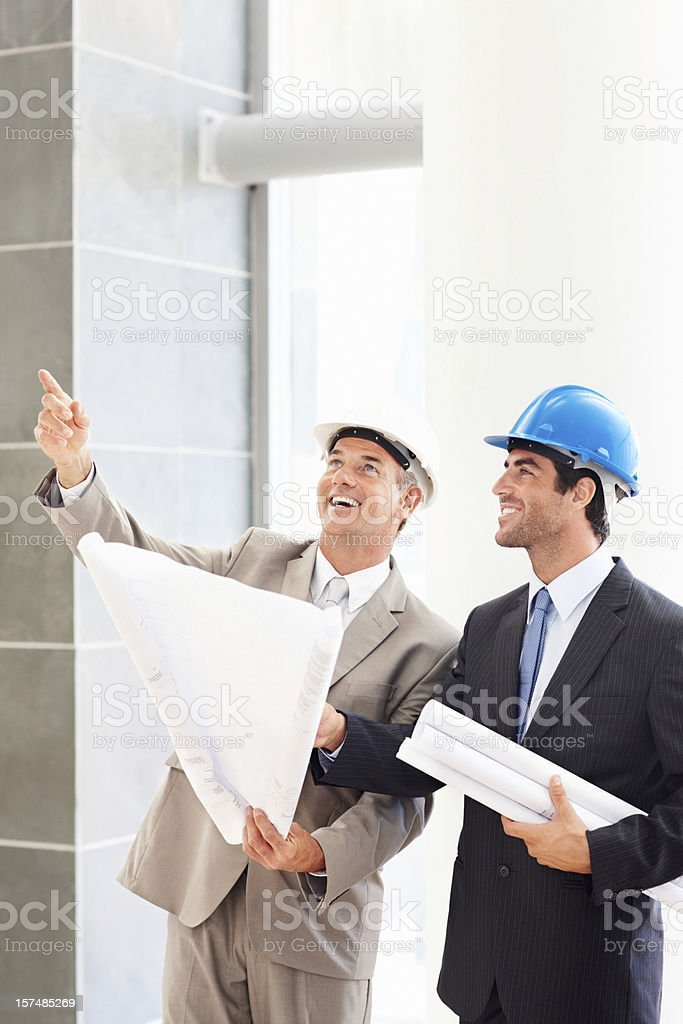 Business colleagues with blueprints and discussing royalty-free stock photo