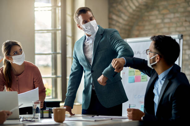 Business colleagues with face masks elbow bumping on a meeting. stock photo