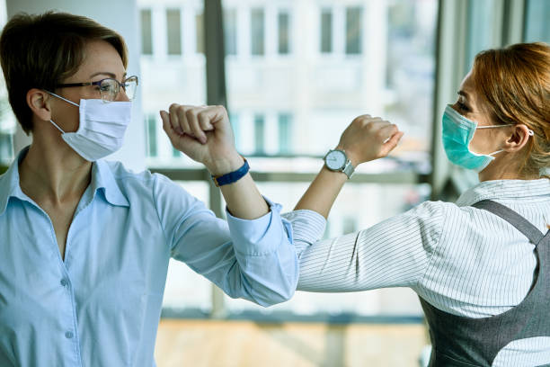 Business colleagues with face masks greeting with elbows during coronavirus pandemic. Two businesswomen elbow bumping while greeting each other in the office during COVID-19 epidemic. flatten the curve stock pictures, royalty-free photos & images