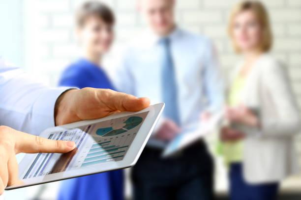 Geschäftskollegen arbeiten und analysieren Finanzkennzahlen auf einem digitalen Tablet – Foto